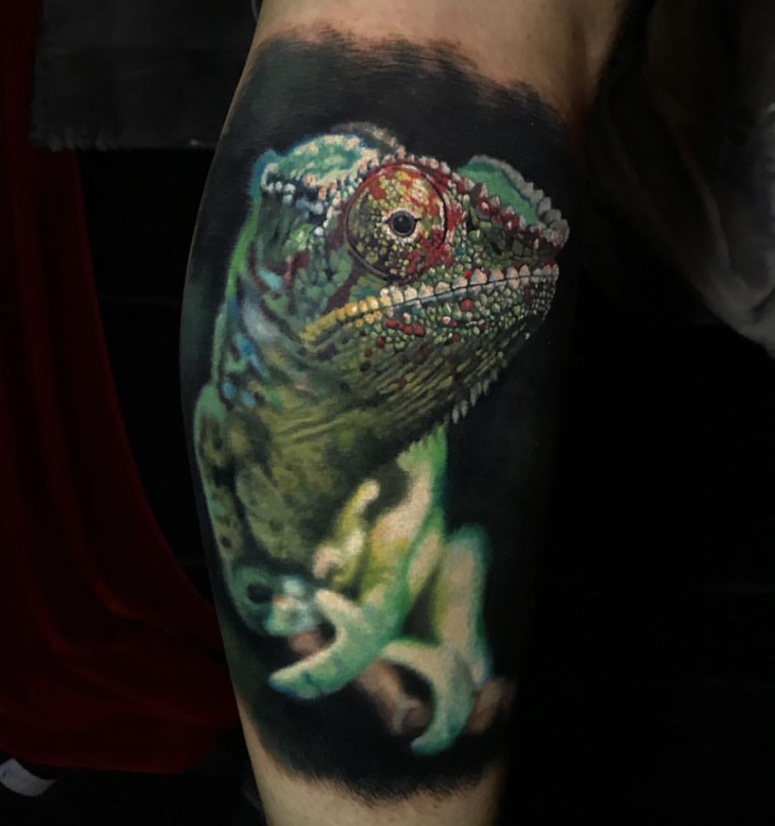 This chameleon tattoo is a perfect example of a macro photo used as a reference, making for a dramatic closeup appearance where the creature's face hovers in space.